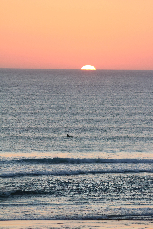 surfeur seul à l'eau sous le soleil couchant